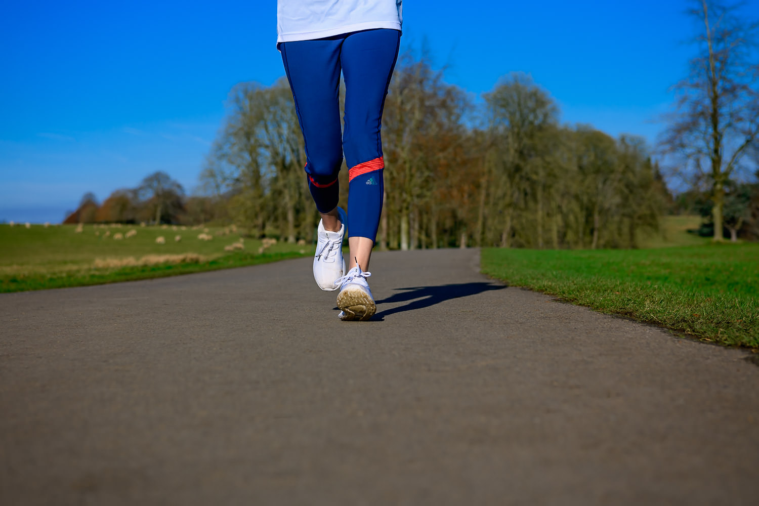 Woman running towards the camera in blue leggings and white trainers