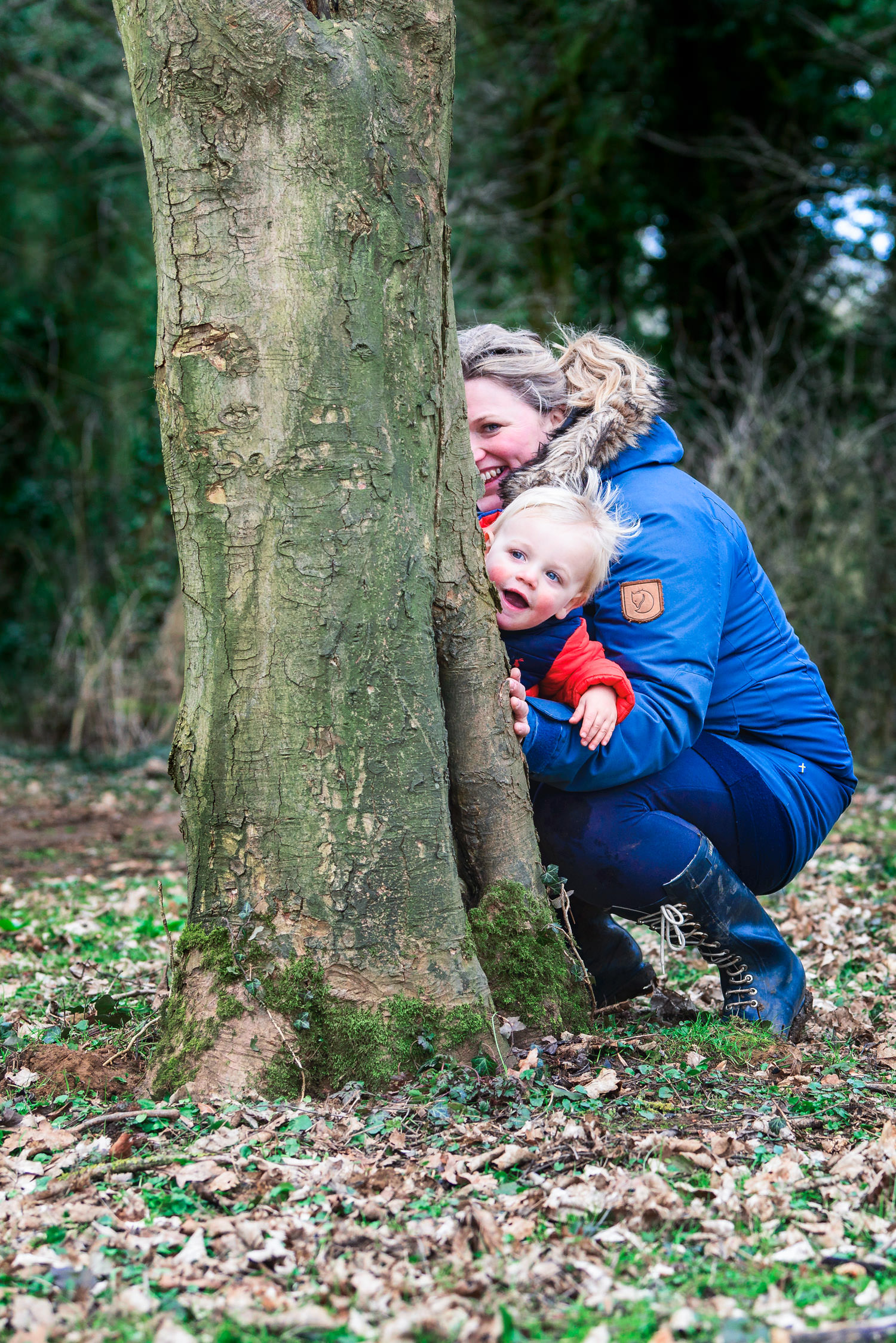 Mum and toddler hiding behind a tree at forest school