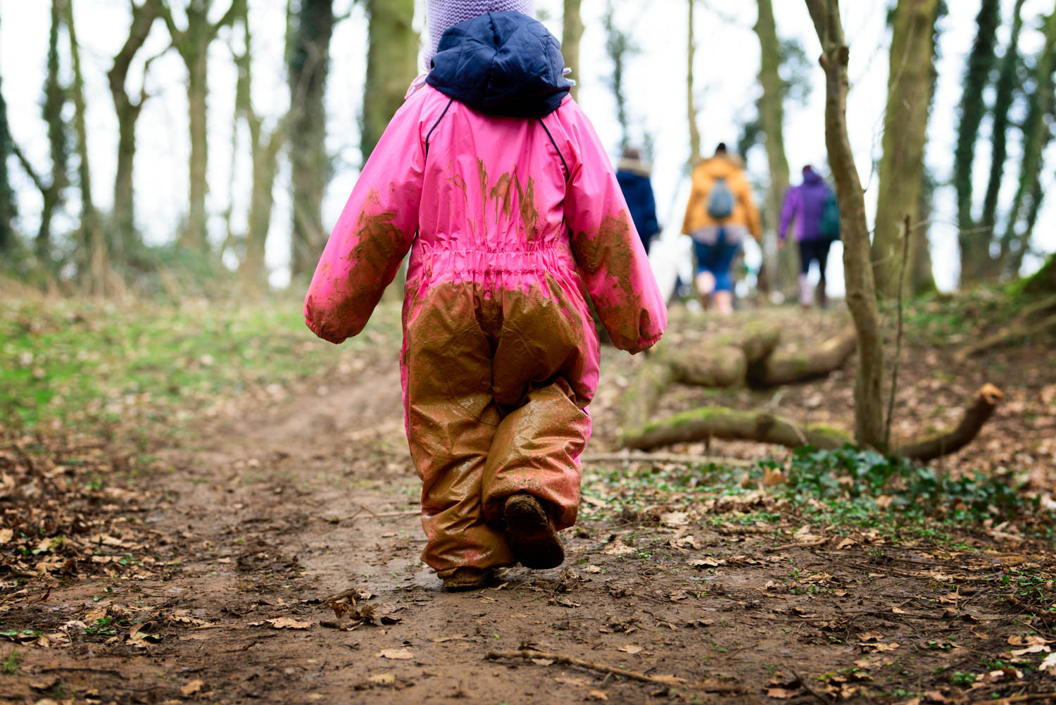 Girl walking away from the camera covered in mud at forest school